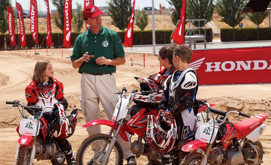 Tres niños con equipo Honda escuchan a un profesor del curso de conducción infantil encima de sus motos Honda