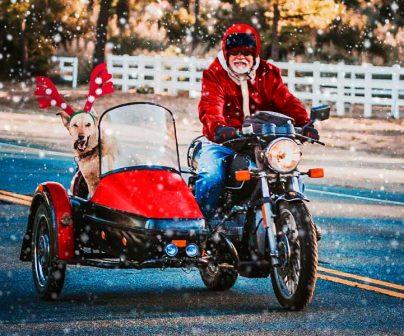 Un sidecar rojo conducido por papa noel y que lleva a un perro rudolf en la cesta