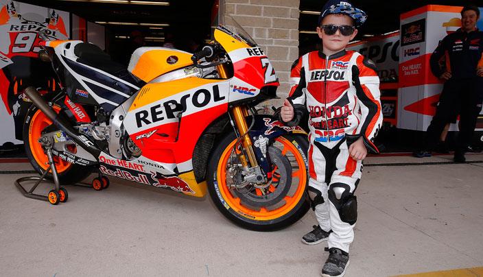 Un joven equipado con un mono Rpesol Honda posa junto a la moto de Dani Pedrosa