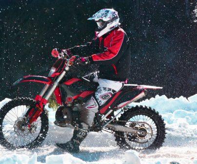 Piloto participando en una carrera de motos off road en la nieve