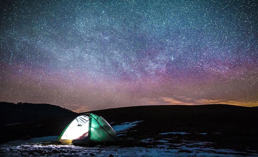 tienda de campanya iluminada en la noche estrellada