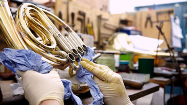 hands cleaning a trumpet