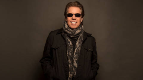 George Thorogood standing with a smile on his face