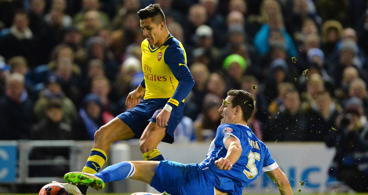 Brighton's Lewis Dunk slides in on Alexis Sanchez of Arsenal