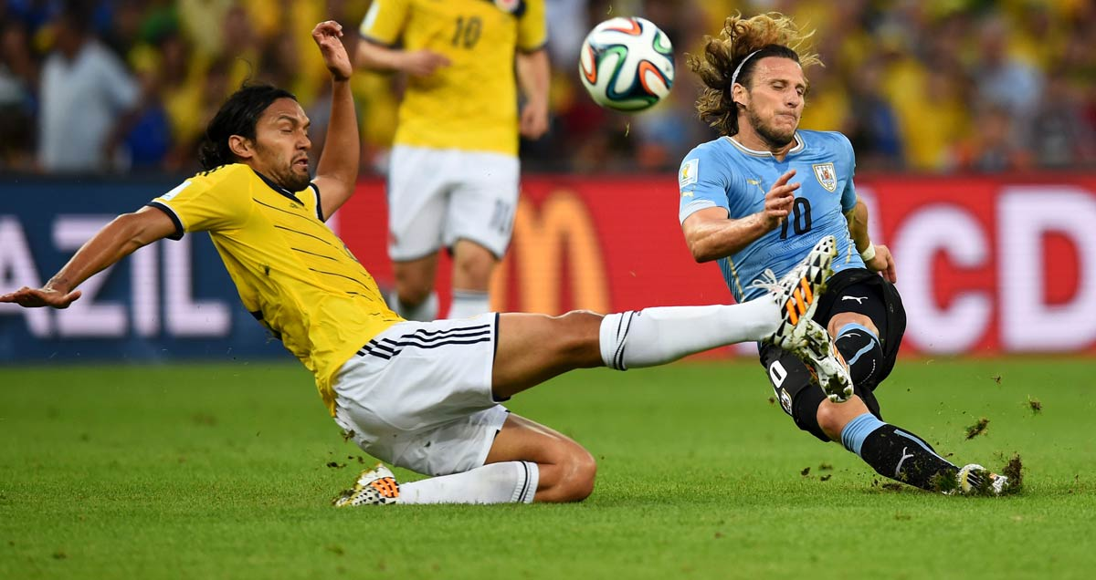 Diego Forlan goes in for a challenge against Colombia