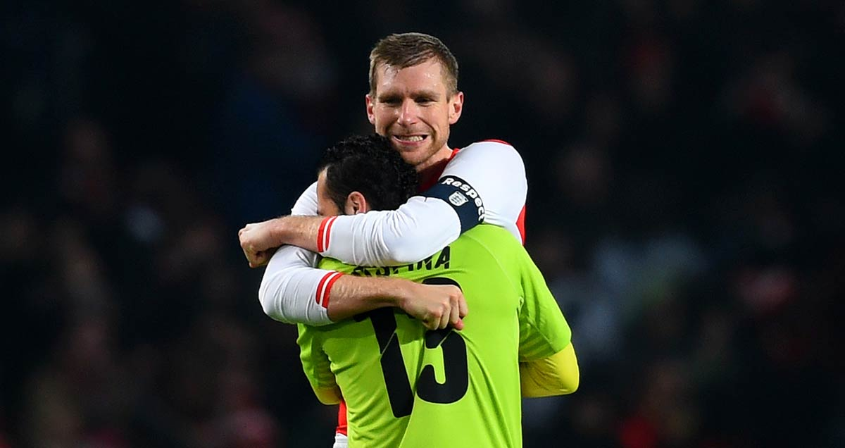 Per Mertesacker embraces Arsenal colleague David Ospina