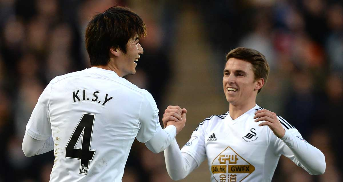 Swansea midfielders Ki-Sung Yeung and Tom Carroll congratulate one another