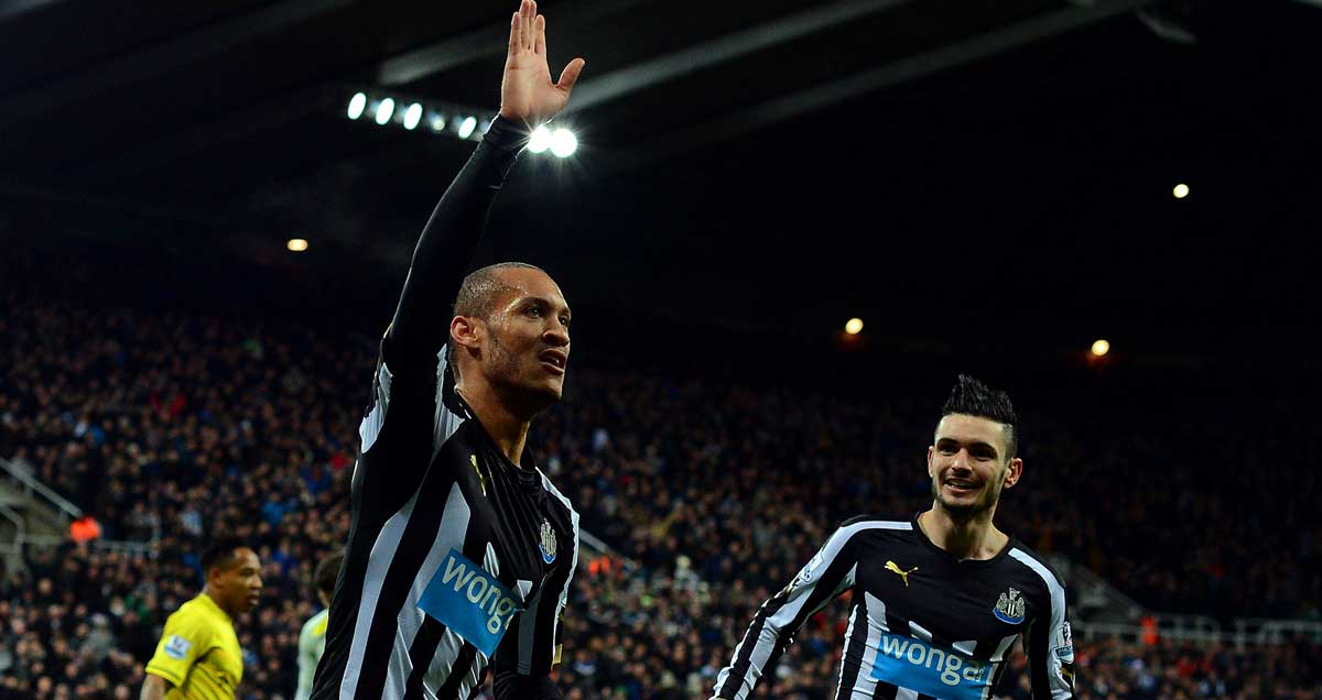 Yoan Gouffran raises an arm aloft and runs away from a chasing Remy Cabella