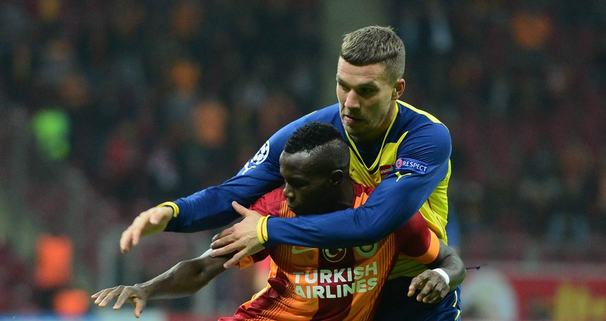 Bruma of Galatasaray is man-handled by Arsenal's Lukas Podoloski