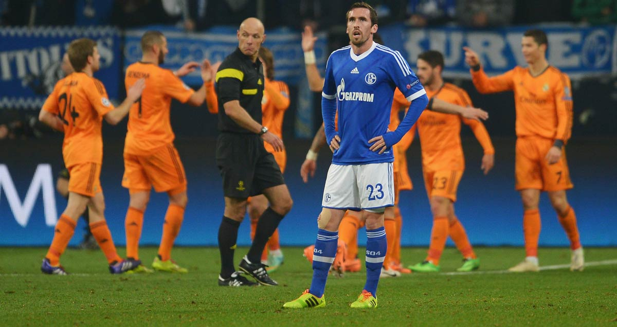 Schalke's Christian Fuchs contemplates a concession as Real Madrid celebrate in the background