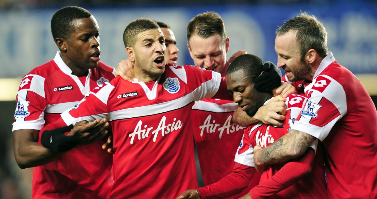 Shaun Wright-Phillips is mobbed by QPR teammates afte scoring at Stamford Bridge in 2013