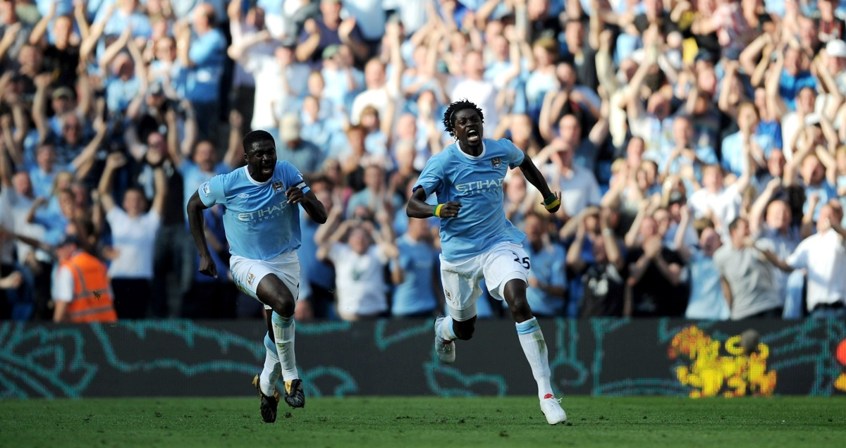 Emmanuel Adebayor sets off to celebrate in front of the Arsenal fans with Kolo Toure in hot pursuit
