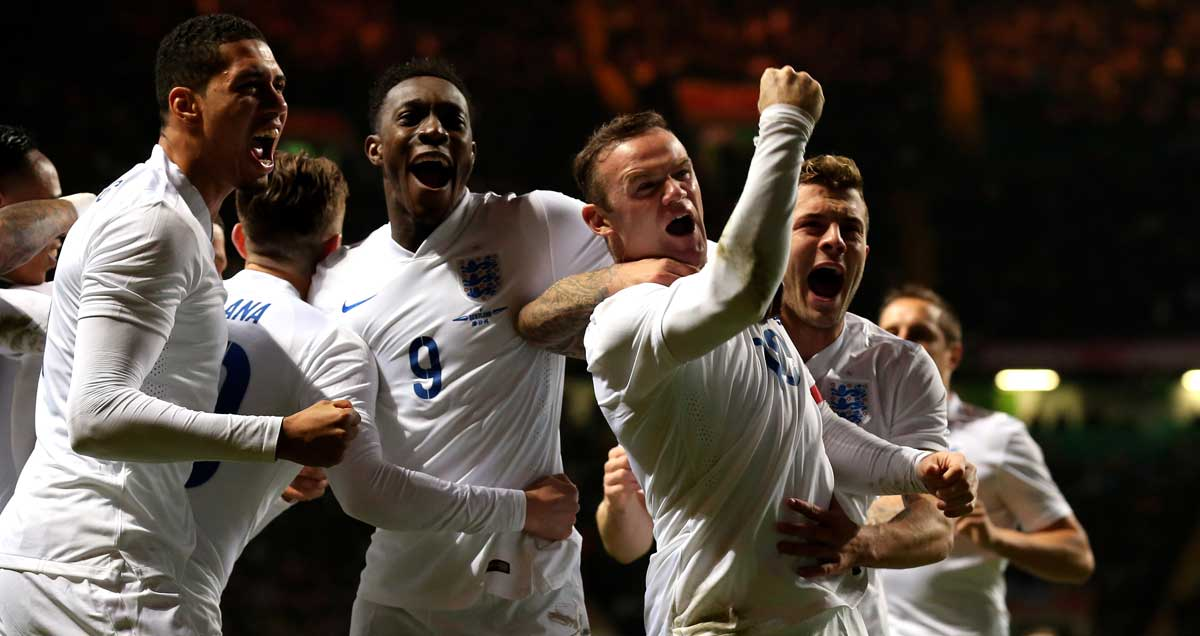 Wanye Rooney mobbed by England teammates after scoring against Scotland