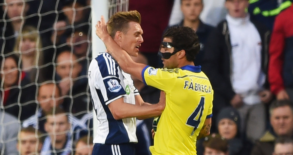 Cesc Fabregas is assaulted by West Brom's Darren Fletcher
