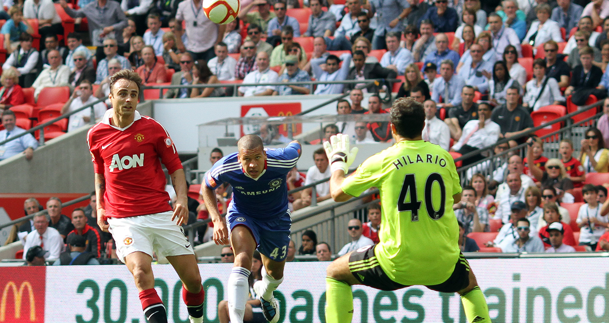 Dimitar Berbatov lofts an injury-time third over Henrique Hilario of Chelsea in the 2010-11 Community Shield