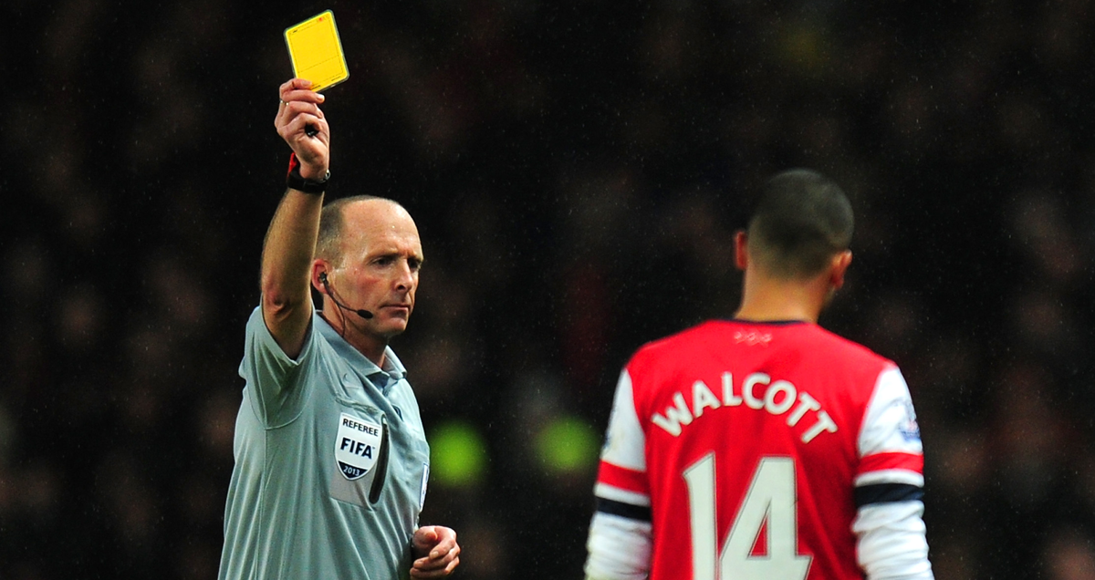 Mike Dean books Arsenal forward Theo Walcott during their game against Chelsea in December 2013