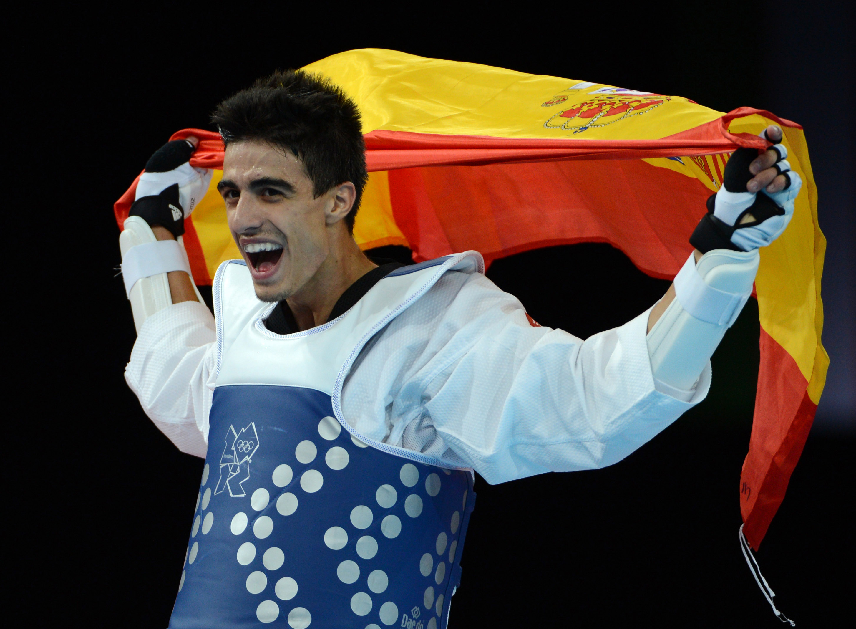 Spain's Joel Gonzalez Bonilla celebrates his victory over South Korea's Lee Daehoon at the end of their men's taekwondo gold medal bout in the category under 58 kg as part of the London 2012 Olympic games, on August 8, 2012 at the ExCel centre in London. AFP PHOTO / TOSHIFUMI KITAMURA (Photo credit should read TOSHIFUMI KITAMURA/AFP/GettyImages)