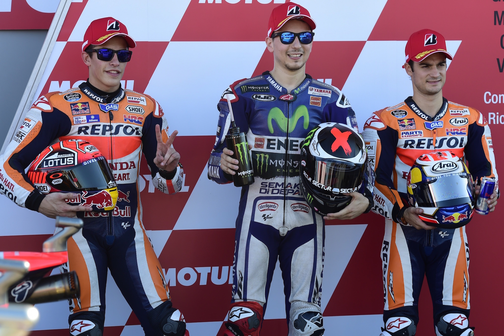 Repsol Honda's Spanish rider Marc Marquez (L), Movistar Yamaha's Spanish rider Jorge Lorenzo (C) and Repsol Honda's Spanish rider Dani Pedrosa pose after the MotoGP qualifying session on the eve of the Valencia Grand Prix at Ricardo Tormo racetrack in Cheste, near Valencia on November 7, 2015. AFP PHOTO/ JAVIER SORIANO (Photo credit should read JAVIER SORIANO/AFP/Getty Images)