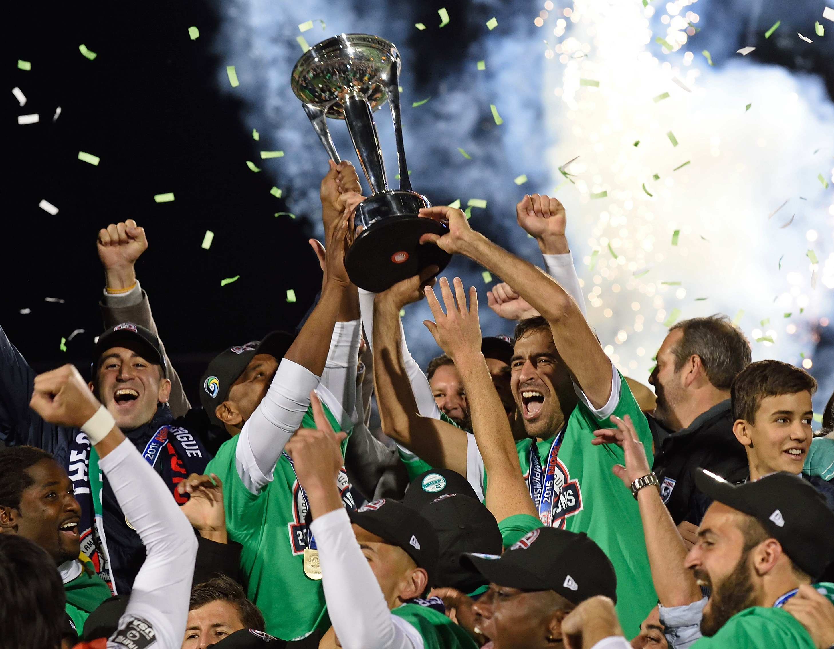 Spanish soccer star Raul (R holding trophy) celebrates with his teammates after the NASL Championship Final match between the NY Cosmos and the Ottawa Fury November 15, 2015 in Hempstead, NY. Raul has planned to retire after the match. AFP PHOTO/DON EMMERT (Photo credit should read DON EMMERT/AFP/Getty Images)