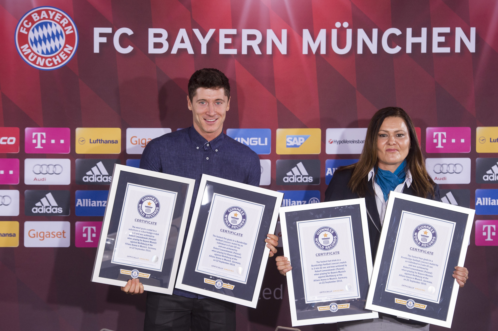 MUNICH, GERMANY - NOVEMBER 30: Robert Lewandowski poses with his four Guinness World Record certificates next to Guinness World Records adjudictor Seyda Subasi-Gemici after a press conference at Saebener Strasse training ground on November 30, 2015 in Munich, Germany. (Photo by Lennart Preiss/Bongarts/Getty Images)