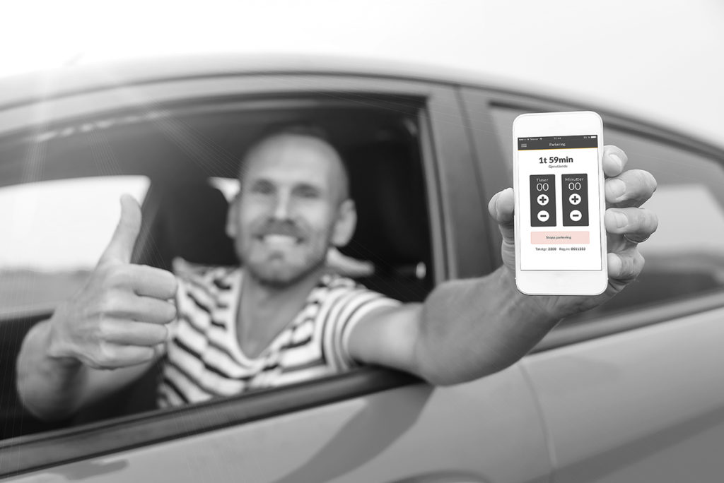 Man in car showing smart phone display and showing thumb up. Focus on mobile phone.