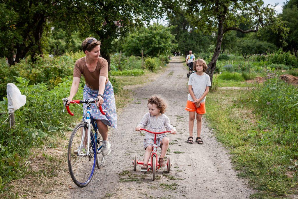 En dame og to barn sykler og går langs en setervei.