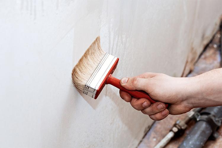 Voorstrijken van een muur voor het behangen