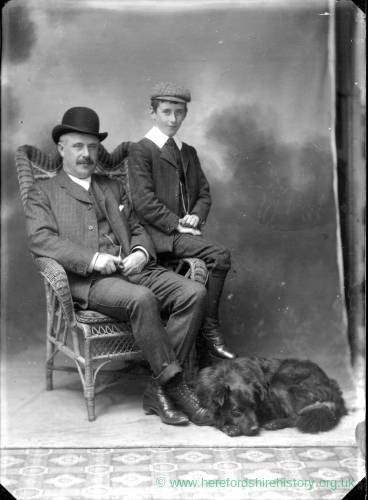 G36-273-13 Father and son portrait, father seated, son perched on arm of chair, dog at feet.jpg