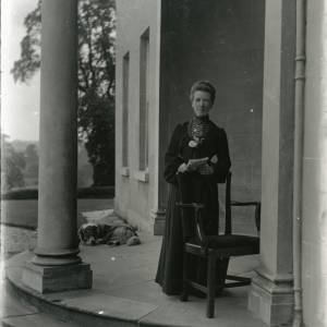 G36-218-08 Older lady standing in semi-circular porch of The Weir, Swainshill, Hereford.jpg