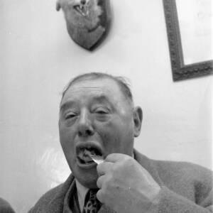 A man eating, stuffed fox head on wall behind.