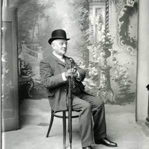 G36-006-14 Man seated with hat on and rolled umbrella. Mr Guy.jpg