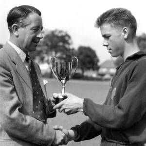 A young boy receiving a sports award.