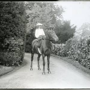 G36-026-05 Girl riding side saddle on horse in driveway.jpg