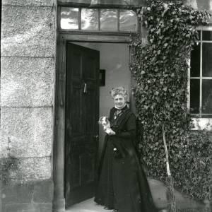 G36-212-12 Brinsop Court, older lady as in G36-212-01, now standing in doorway holding puppy.jpg