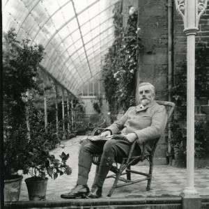 G36-027-04 Man wearing breeches seated in wicker chair on glazed verandah.jpg