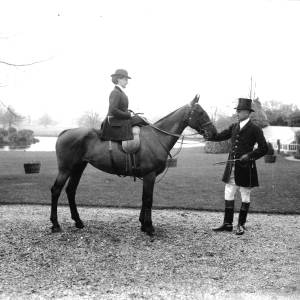 G36-254-04 Lady, as in G36-254-02, seated side saddle on a hunter whose head is held by a huntsman.jpg