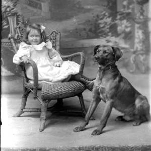 G36-135-11 Portrait little girl seated on wicker chair with large dog beside her.jpg