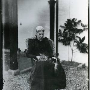 G36-002-03 Lady in chair outside house with cat on knee Field Farm House Hampton Bishop.jpg