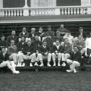 G36-429-04 Group of 21 cricketers and 2 umpires at Hereford Racecourse pavilion.jpg