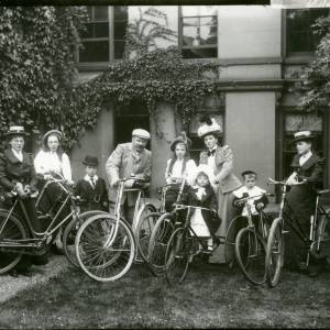 G36-014-13 Family group with bicycles in garden of house (one little girl, two older girls, two boys, three women and one man).jpg