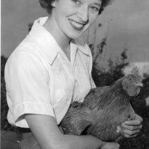 A smiling young lady holding a chicken.