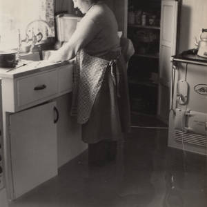 Lady washing up, standing in a flooded kitchen.