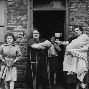Welsh women and children in the doorway of a stone house.