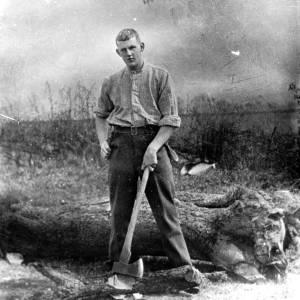 G36-549-18 Man with an axe, beside a felled tree.jpg