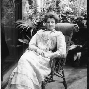G36-035-06 Lady seated in wicker chair (possibly in a conservatory) with potted palms and flowers behind her.jpg