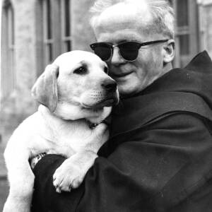 A monk at Belmont Abbey holding a labrador puppy.