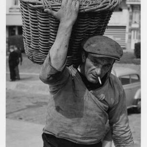 484 - Man smoking cigarette and with basket of shrimps on his back