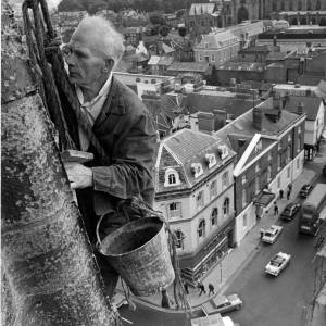 A workman high up All Saints church in Hereford.