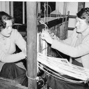 Two women weaving.