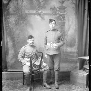 G36-034-07 Two soldiers, Herefordshire Rifle Volunteer Corps. One with a swagger cane, both smoking and wearing forage caps and puttees. Studio portraits .jpg